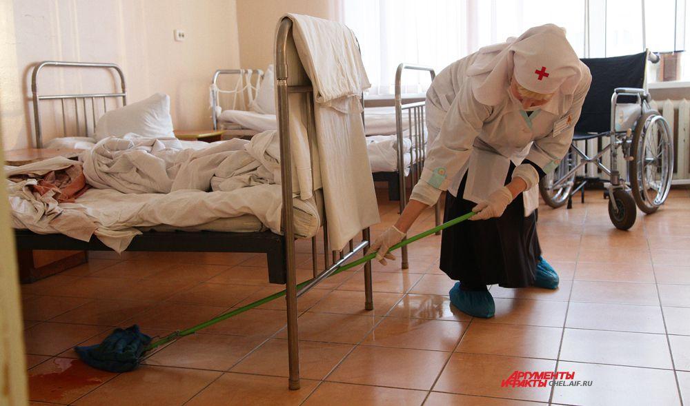 Сестра Мария убирает за пациентом.