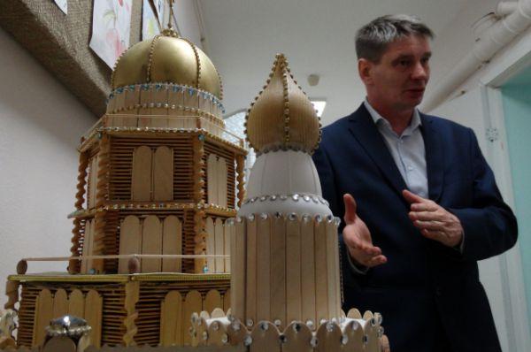 Социальный работник Ханты-Мансийского ПНД Василий Кучин показывает модель храма, которую его подопечный сделал, используя палочки от эскимо.