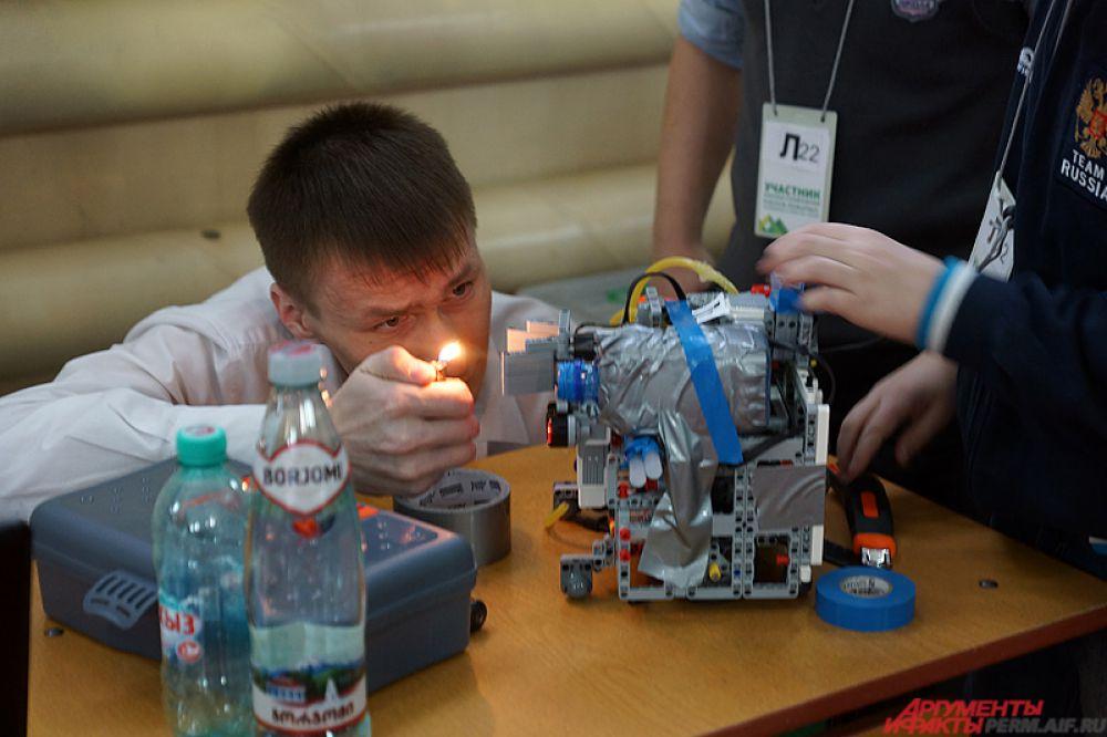 Школьник тестирует своего робота перед выходом на арену.