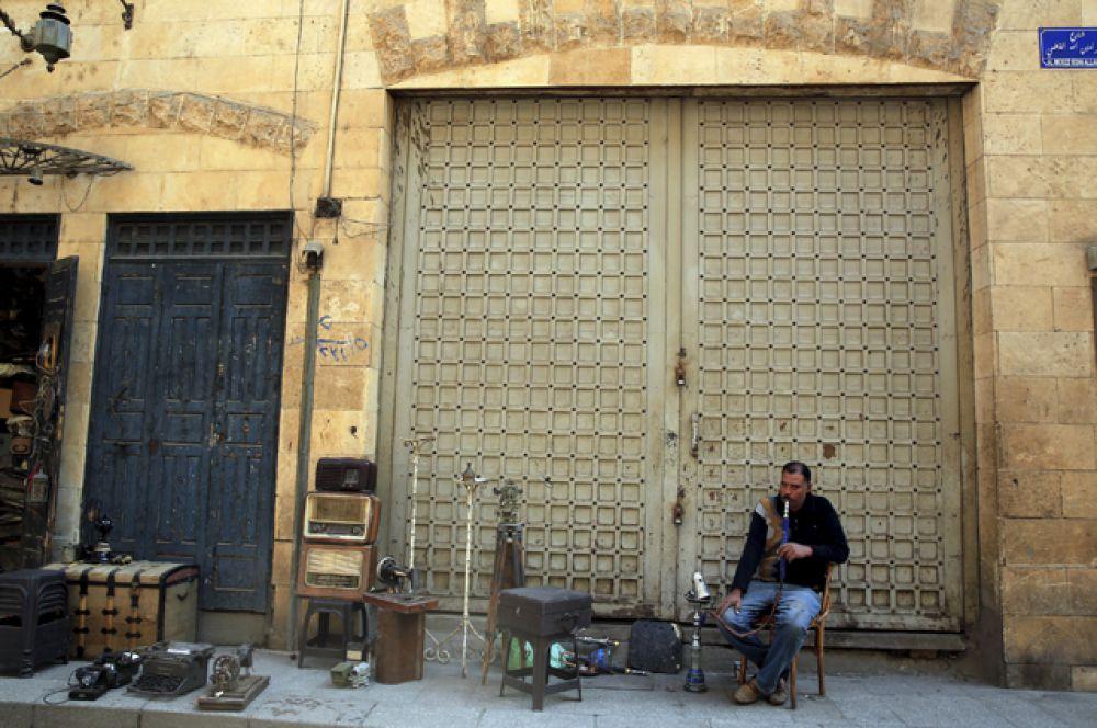 Владелец магазина в ожидании покупателей на популярном туристическом рынке Хан-эль-Халили в старом городе Каира.