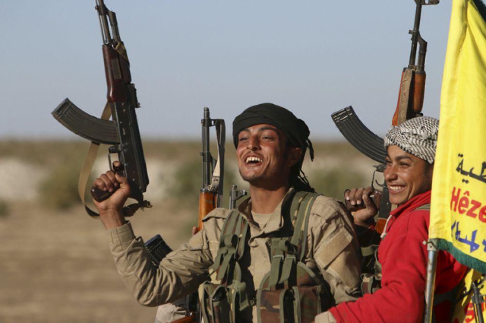 Бойцы курдско-арабского союза сирийских демократических сил с поднятым вверх оружием в знак захвата города Аль-Хоул, Хасака.