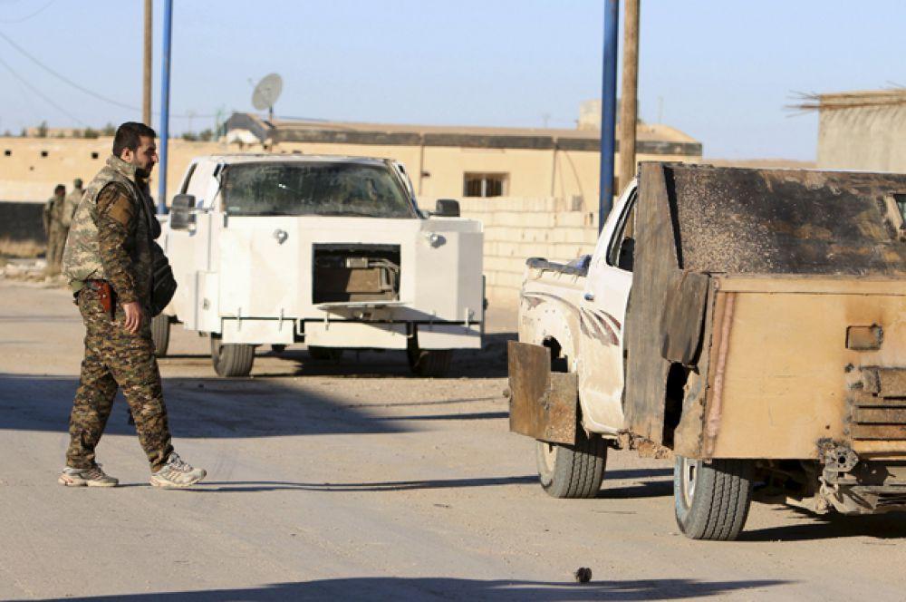 Бойцы из демократических сил Сирии около автомобилей, принадлежавших исламским боевикам и оснащенных взрывчаткой в сирийском городе Аль-Хоул.