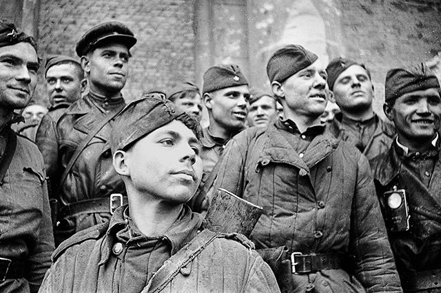 19-летний Григорий Булатов на ступенях рейхстага (на переднем плане).