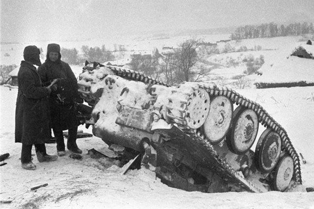 Два красноармейца стоят рядом с перевернутым немецким танком, подбитым в сражении под Москвой.