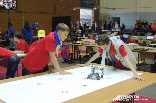 Школьники-разработчики проверяют, как их робот справляется с заданием на поле.