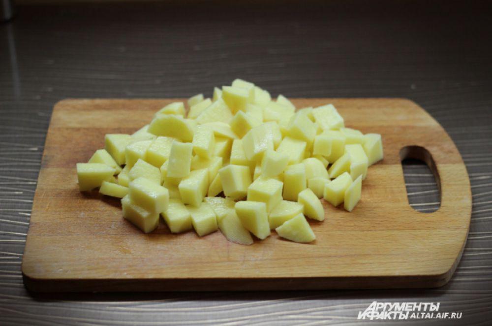 Когда мясо готово, достаем его из кастрюли и продолжаем готовить. Режем картофель на небольшие кубики и опускаем в кастрюлю. Варим на среднем огне, суп не должен кипеть.