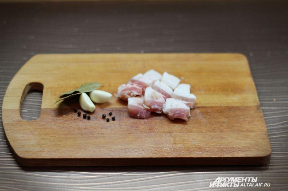 Сало режем на небольшие кусочки. Чистим чеснок.