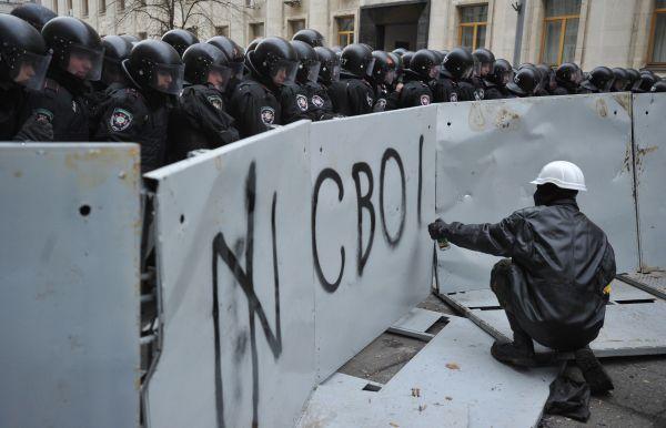 Участник акции пишет слово «Свобода» на металлическом заграждении перед отрядом «Беркута».