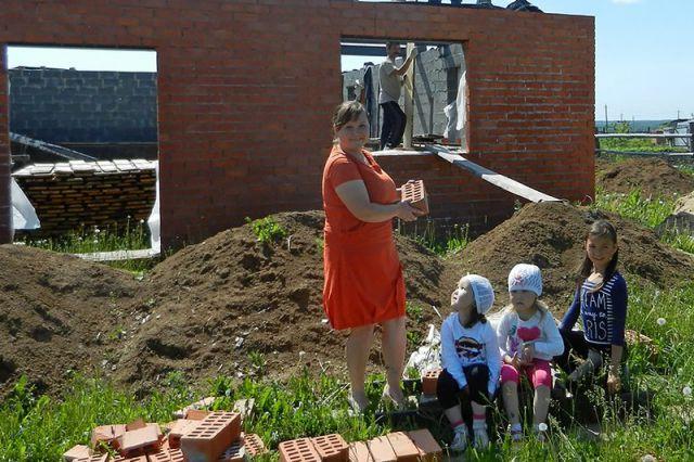 Получив землю, многодетная семья строит дом