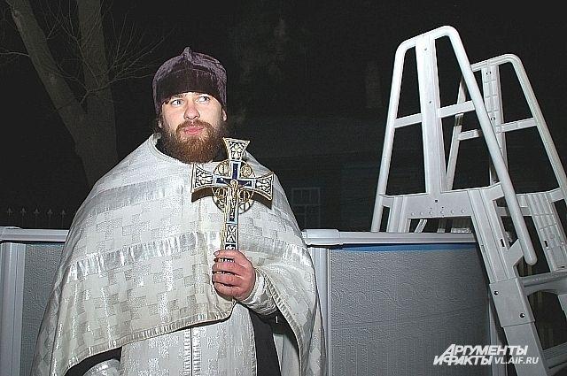 Священник освещает воду в купели.