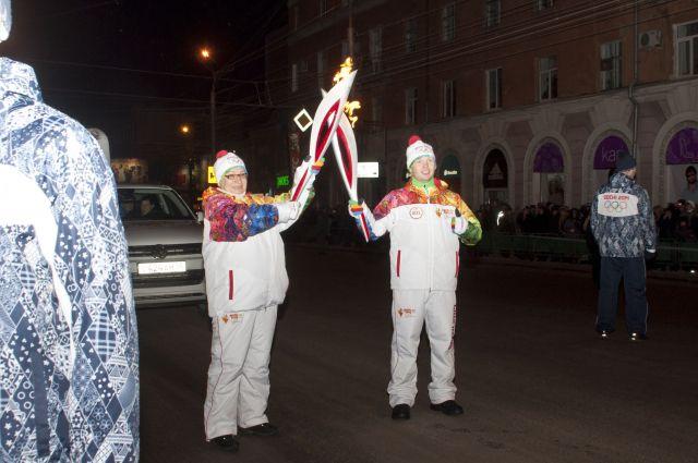 Олимпийский огонь переходит от факелоносца к факелоносцу.