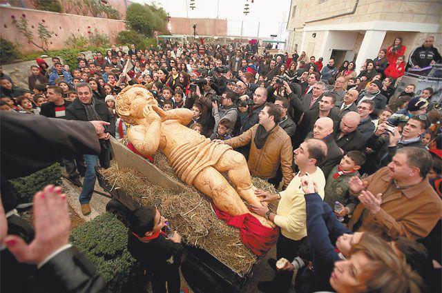Статую младенца Христа встречают толпы верующих христиан.