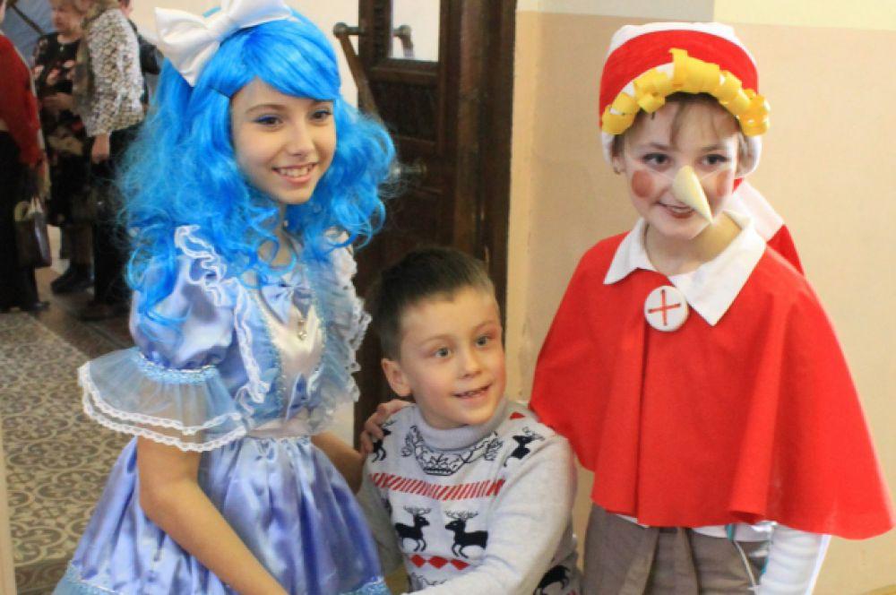 Маленькие гости мероприятия фотографируются с Буратино и Мальвиной.