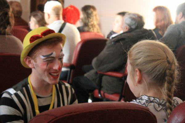 С детьми, пришедшими на концерт, играет клоун. Счастливы все: и гости, и их родители, и сами участники