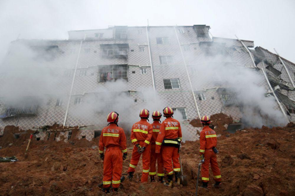 Работники пожарной службы на месте схода оползня в Китае.