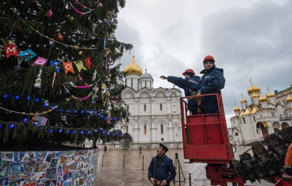 Рабочие украшают Новогоднюю ёлку на Соборной площади Кремля в Москве.