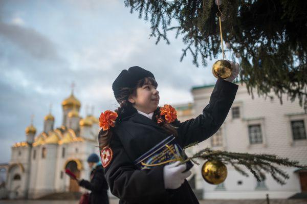 Кадет украшает Новогоднюю ёлку на Соборной площади Кремля в Москве.