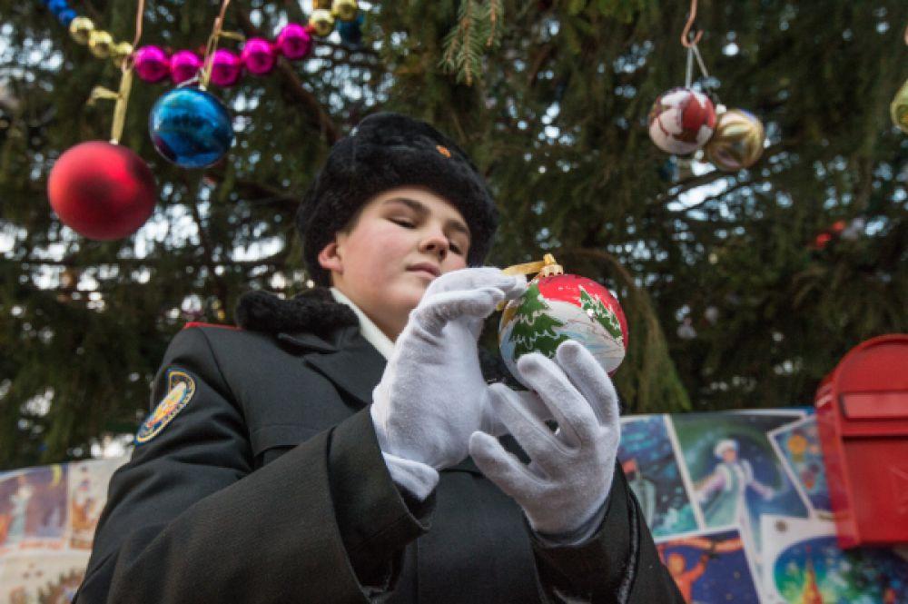 адет держит ёлочную игрушку у Новогодней ёлки.