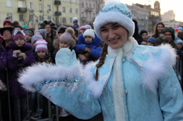 На сцене начинается музыкальный концерт. Дед Мороз и Снегурочка приветствуют собравшихся.