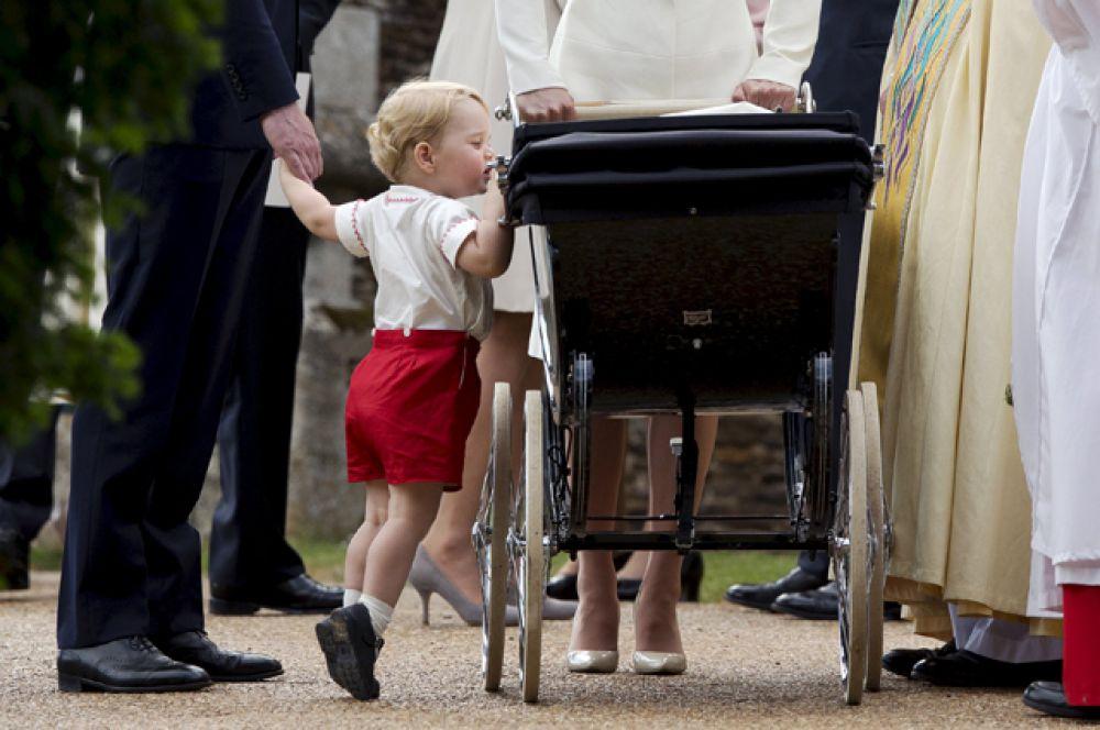 Британский принц Джордж заглядывает в коляску своей сестры принцессы Шарлотты после ее крещения в церкви Святой Марии Магдалины, 5 июля 2015.