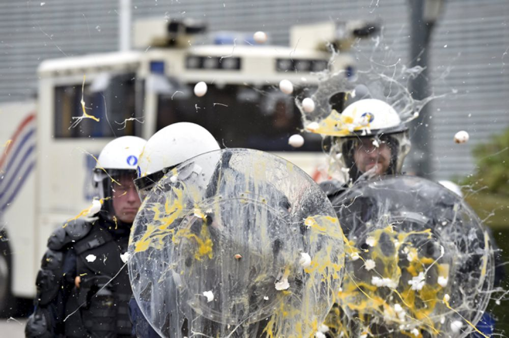 Полицейских закидывают яйцами на акции протеста фермеров во время чрезвычайного заседания министров сельского хозяйства ЕС в Брюсселе, 7 сентября 2015.