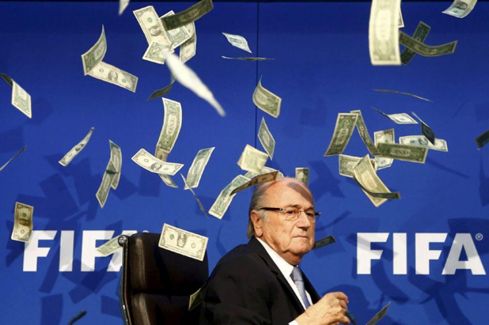 Британский комик Ли Нельсон бросает банкноты в президента ФИФА Зеппа Блаттера во время пресс-конференции после внеочередного совещания исполнительного комитета федерации в штаб-квартире ФИФА в Цюрихе, 20 июля 2015 года.