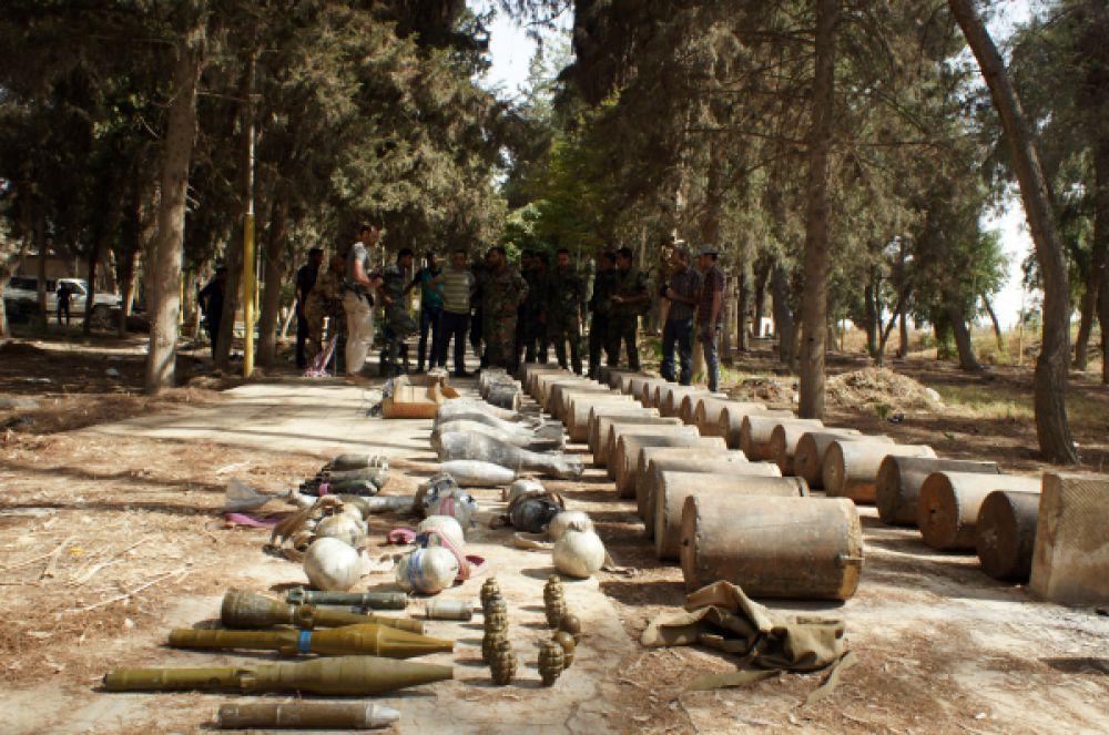 Сирийские военнослужащие досматривают трофеи, захваченные у боевиков ИГИЛ в Сирии, 30 июля 2015.