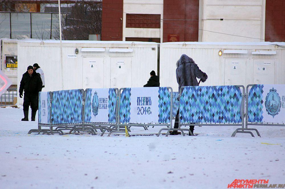 На эспланаде рабочий убирает мусор с ледового городка.