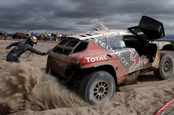 Французские гонщики Сирил Десперс и Давид Кастера пытаются вытолкнуть свою машину из песка.