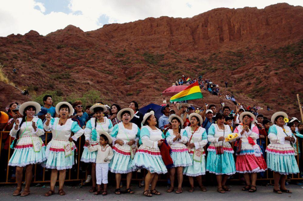 Боливийские женщины поддерживают участников гонок танцами и песнями.