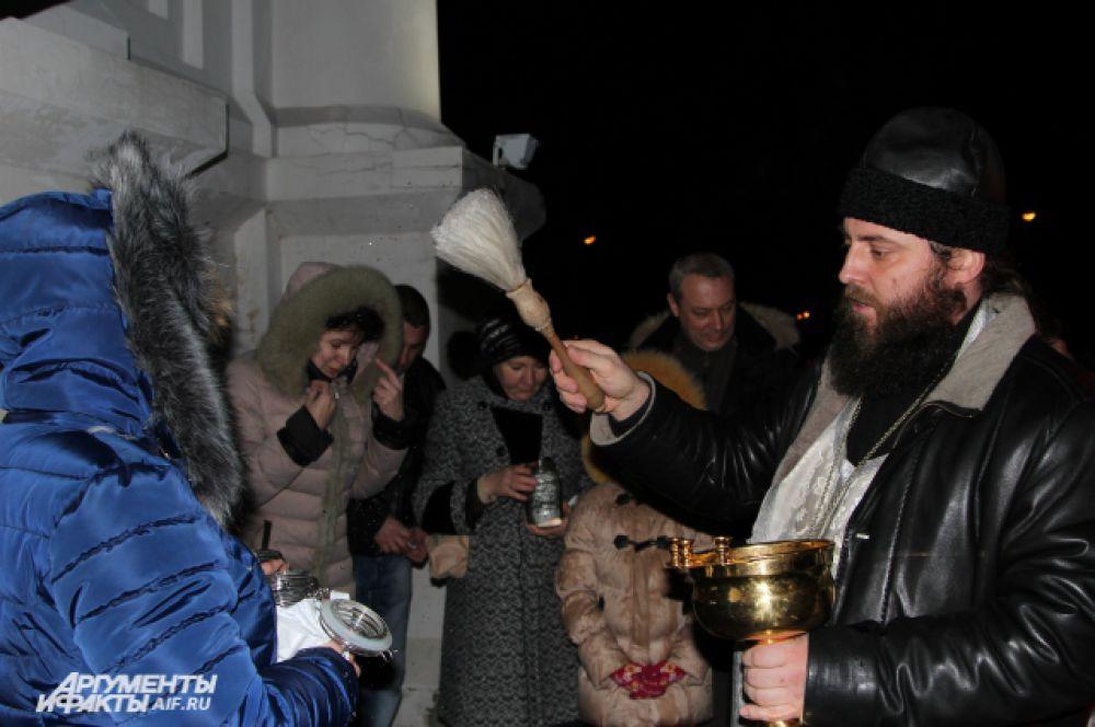 При входе в храм служитель церкви проводил обряд освящения воды.