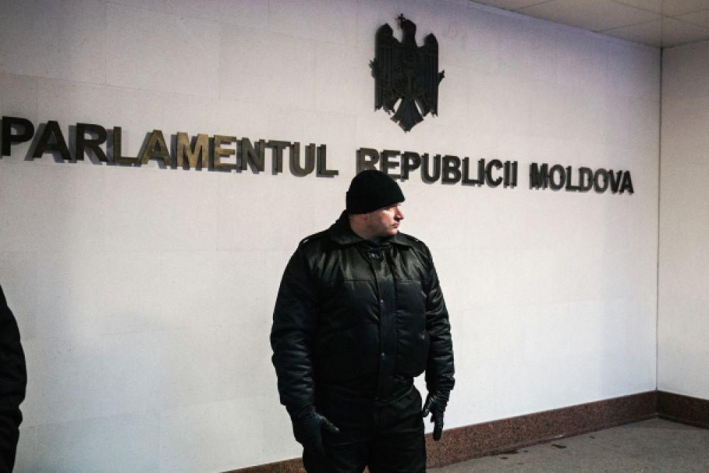 Сотрудник правоохранительных органов у здания парламента в Кишиневе. В среду парламент Молдавии утвердил новый состав кабинета министров во главе с Павлом Филипом.