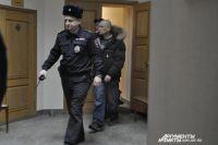 Илья Азовский в сопровождении конвоя проходит в зал суда.