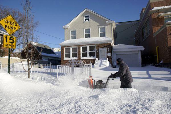 Мужчина чистит улицу возле своего дома в Нью-Йорке.