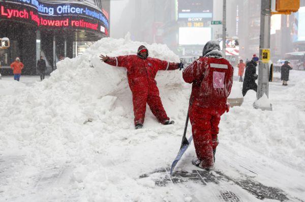 Сотрудники снегоуборочной команды фотографируются на фоне сугроба на Таймс-сквер.