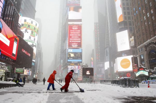 Рабочие убирают снег во время метели на Манхеттене.