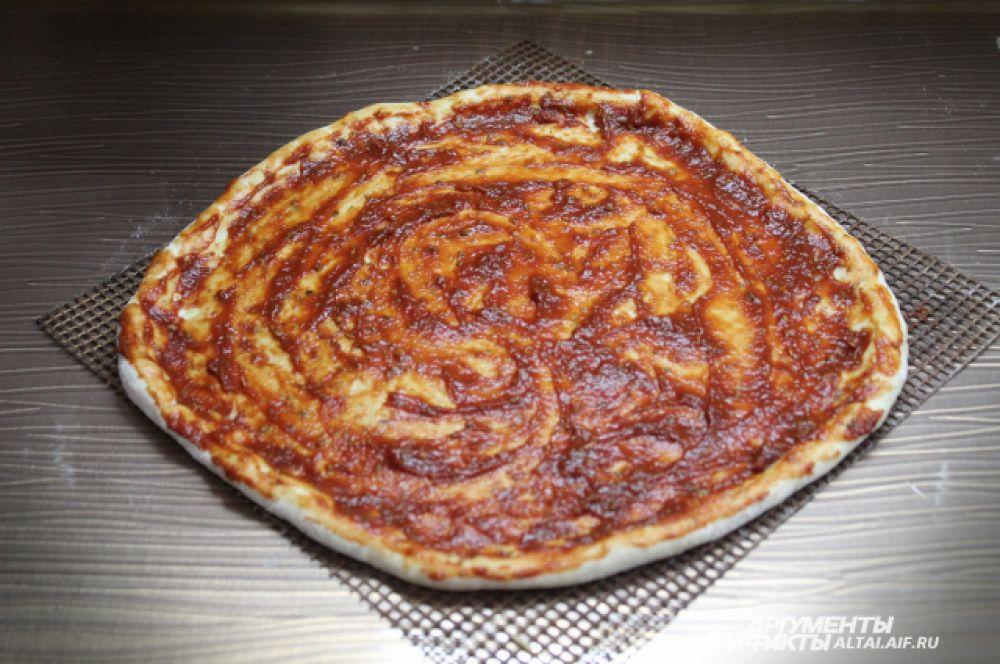 Смазываем тесто томатной пастой с добавлением орегано.