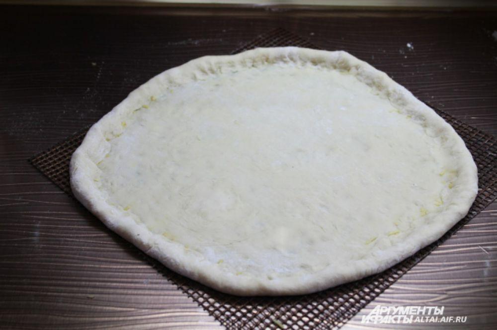 Делаем сырный бортик, аккуратно защипывая края пиццы вовнутрь.