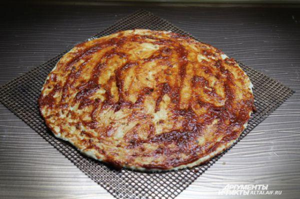Вторую пиццу я сделаю без сырного бортика. Раскатываю тесто и смазываю оставшейся томатной пастой.
