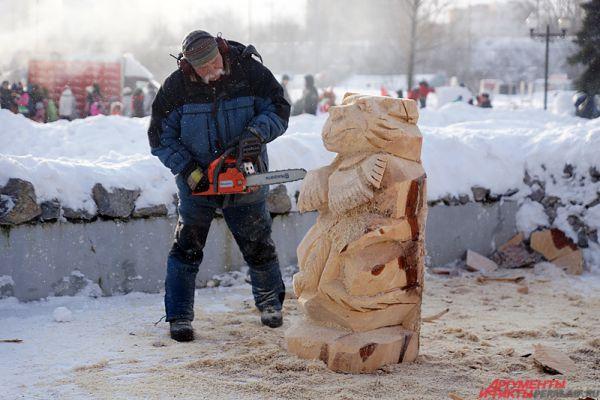 Художник рядом с снежными скульптурами выпилил из дерева медведей.