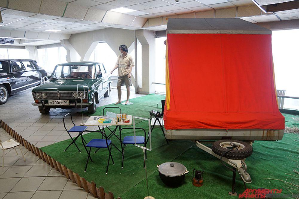 Зелёный «Жигули» находится в так называемом «дачном» арт-пространстве – около машины имеется зелёный коврик, напоминающий траву, рядом установлены палатка и столик с консервами.