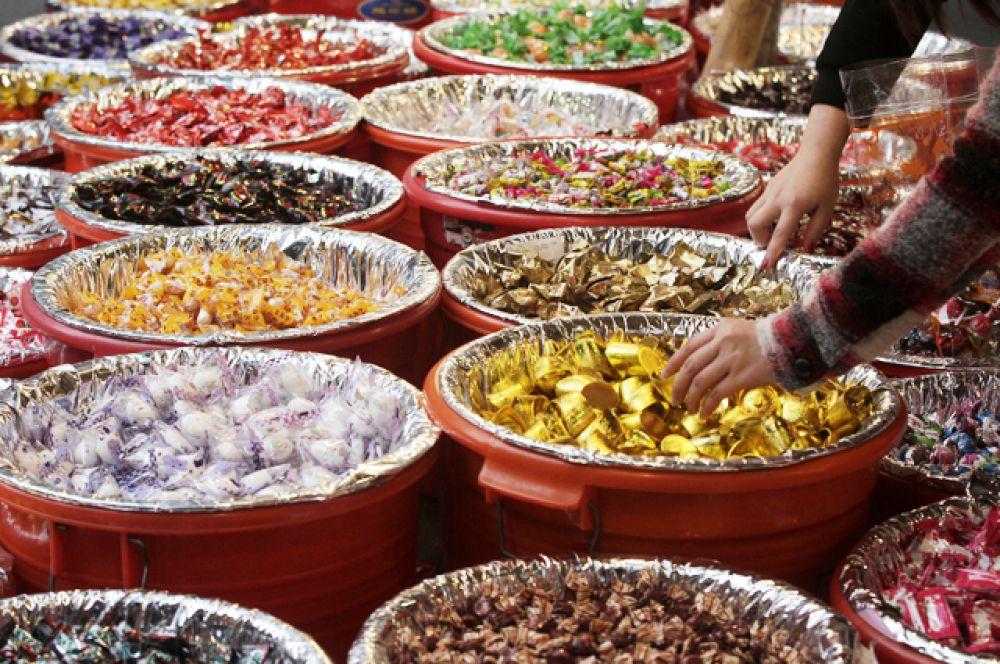 Люди покупают конфеты на рынке в Тайбэе.