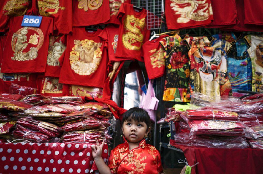 Девочка примеряет платье в китайском квартале Бангкока.