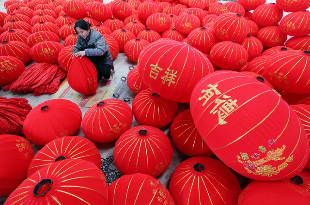Рабочий на фабрике по изготовлению китайских фонариков.