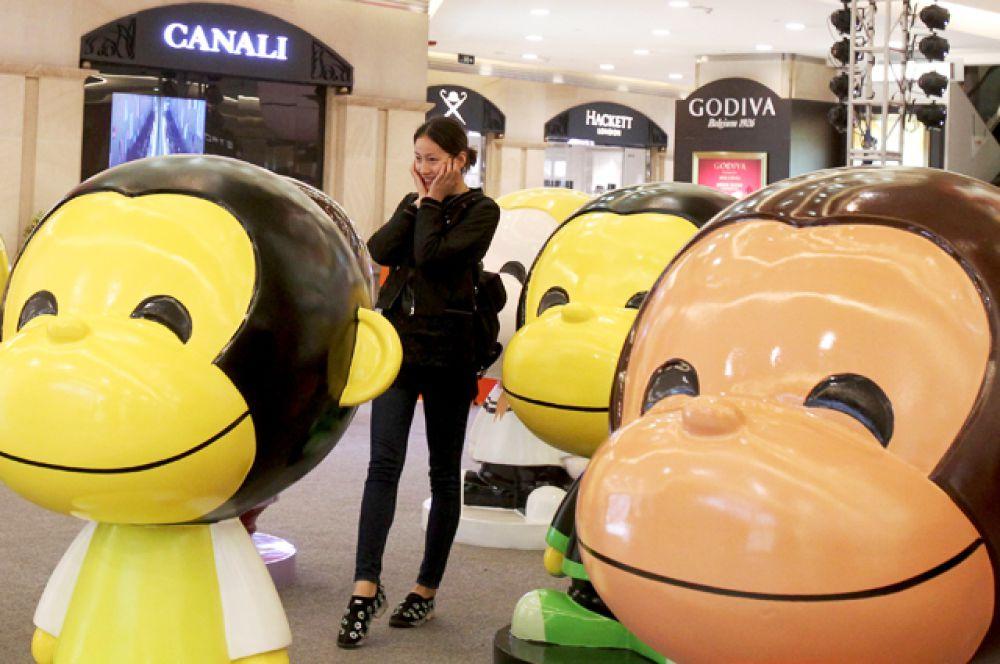 Девушка фотографируется среди обезьян в торговом центре в Шанхае.