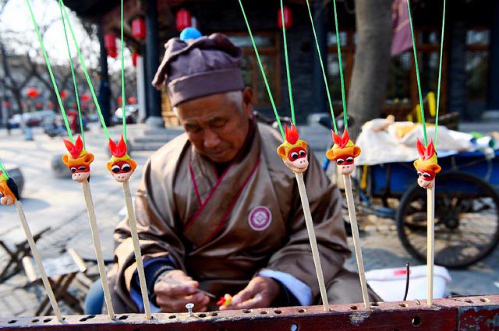 Художница делает фигурки обезьян из теста, провинция Шаньдун.