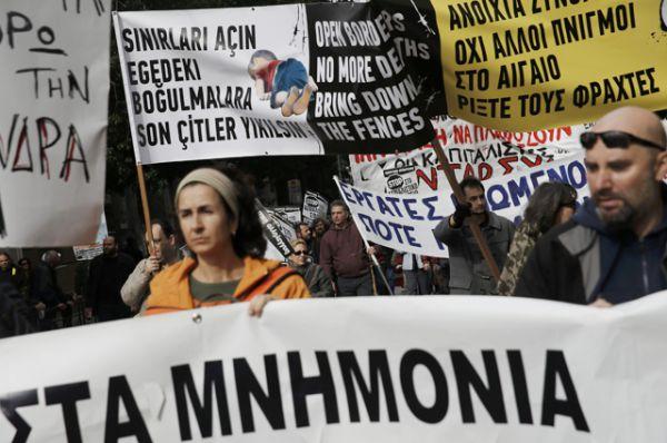 Демонстранты на марше во время 24-часовой всеобщей забастовки против запланированных пенсионных реформ в Афинах, Греция.