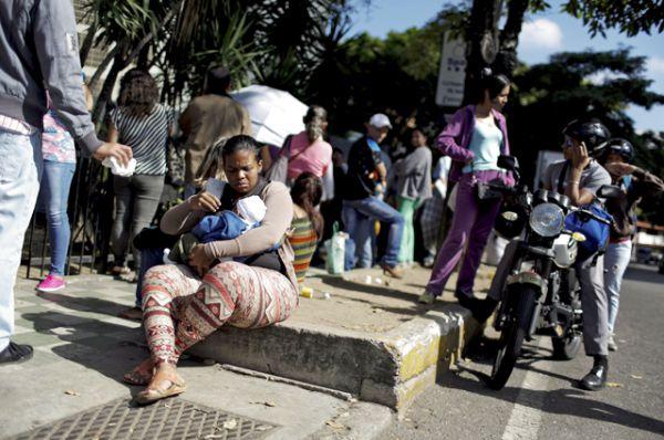 Женщина с ребёнком  в очереди перед супермаркетом в Каракасе.