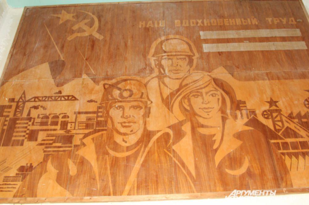 Внутрь здания «Гуковской» мы, как и на «Алмазной», попадаем беспрепятственно. Парадная дверь открыта, коридоры пусты. На стене висит большая картина «Наш вдохновенный труд», олицетворяющая шахтёрскую доблесть в советское время.