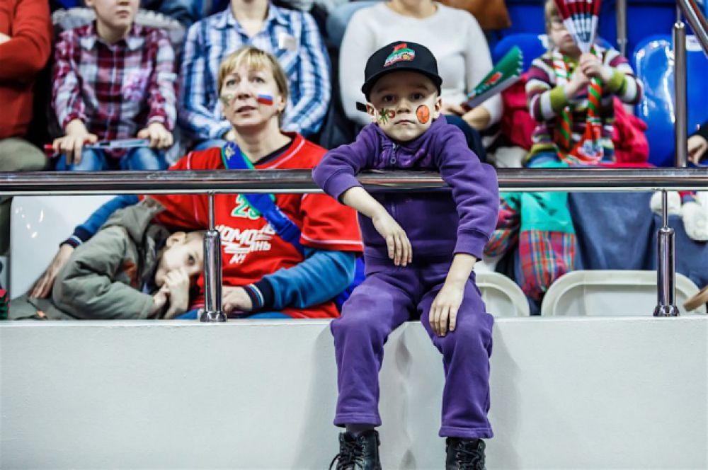 Юный болельщик наблюдает за своими ровесниками-баскетболистами.